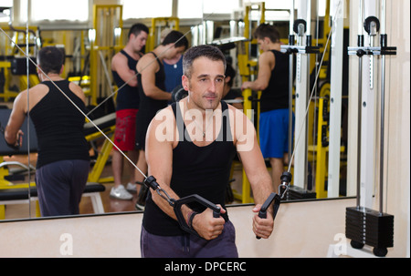 Middle aged man working out with gym equipment, exercising pecs muscles with cables - Stock Photo