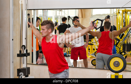 Young man training on gym equipment, pulling handles on cable machine - Stock Photo