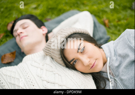 Portrait of young woman resting head on man's chest - Stock Photo