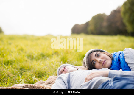Young woman resting head on man's chest in park - Stock Photo