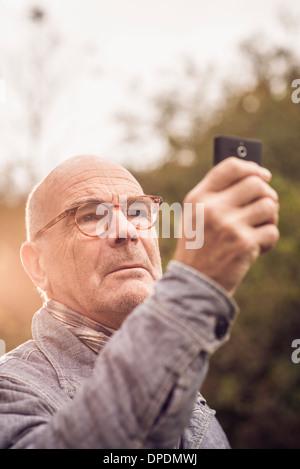 Senior man using cellular phone - Stock Photo