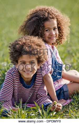 Portrait of brother and sister lying on grass in sunlight - Stock Photo