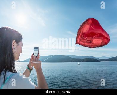 Mature woman photographing heart shaped balloon - Stockfoto