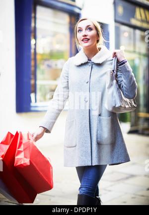 http://n450v.alamy.com/450v/dpdp1y/young-woman-walking-down-street-carrying-shopping-bag-dpdp1y.jpg