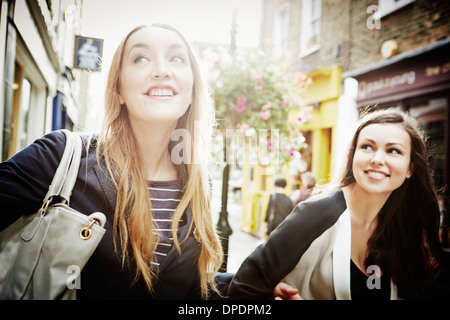 Young women walking down street carrying bags and laughing - Stock Photo