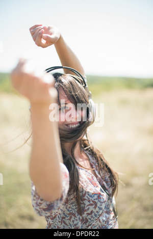 Portrait of mid adult woman dancing in field with arms raised, wearing headphones - Stock Photo