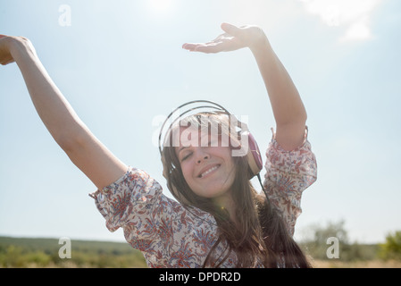 Portrait of mid adult woman dancing in field wearing headphones with arms raised - Stock Photo
