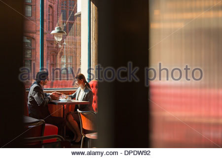 Couple sitting in restaurant booth - Stock Photo