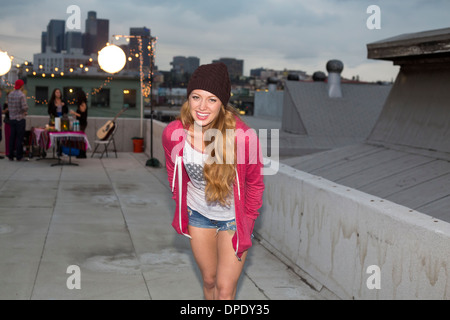 Young woman in wool hat at rooftop barbecue - Stock Photo