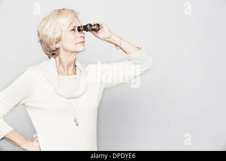 Studio portrait of senior woman looking through binoculars - Stock Photo