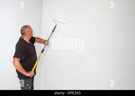 Studio shot of senior roller painting room walls - Stock Photo