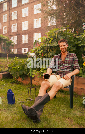 Mid adult man taking a break on council estate allotment - Stock Photo