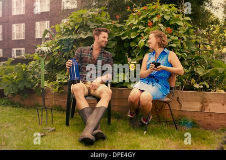 Couple taking a break on council estate allotment - Stock Photo