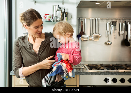 Mother carrying baby girl in kitchen - Stock Photo