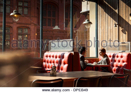 Couple sitting in restaurant booth - Stockfoto