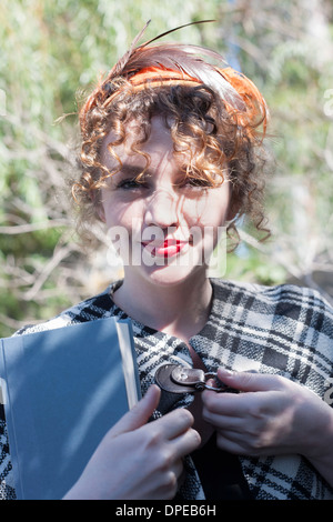 Portrait of young woman holding book in park - Stock Photo