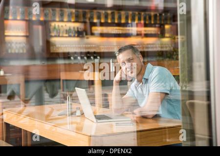 Businessman using laptop, view through window - Stockfoto