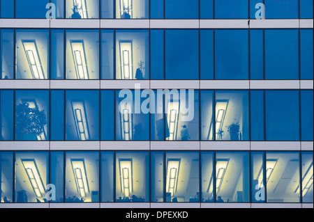 Facade of a modern office building with lights on in the offices in the evening, Munich, Bavaria, Germany - Stock Photo