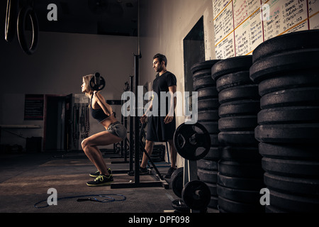 Female weight-lifter being watched by trainer - Stock Photo