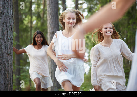 Teenage girls running in forest - Stock Photo
