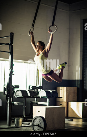 Young woman training on rings in gymnasium - Stock Photo