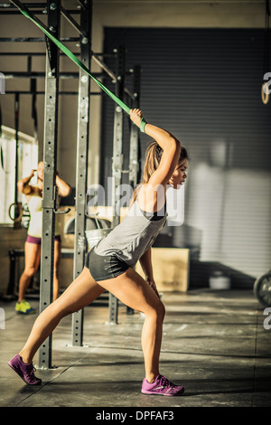 Young woman stretching on exercise bar in gymnasium - Stock Photo