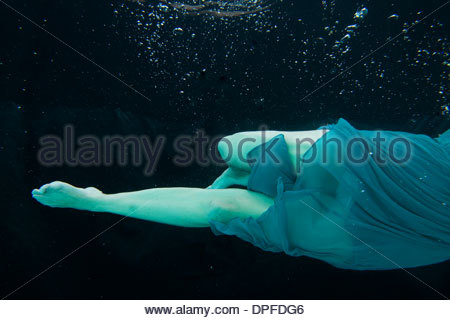 Elegant young woman in dress underwater - Stock Photo