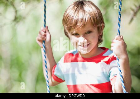 Boy on swing, portrait - Stock Photo