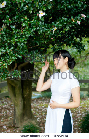 Young woman smiling in woodland park wearing traditional Vietnamese attire. - Stock Photo