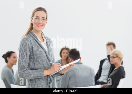 Portrait of therapist with group therapy in session in background - Stock Photo