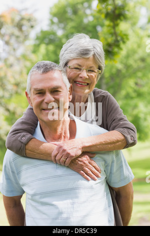 Senior woman embracing man from behind at park - Stock Photo