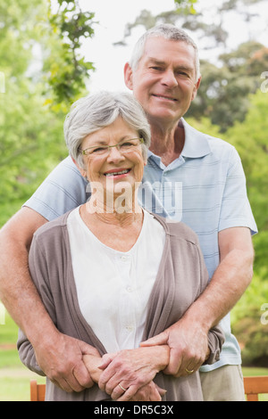 Senior man embracing woman from behind at the park - Stock Photo