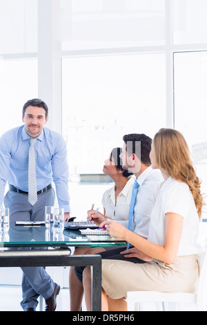 Executives around conference table in office - Stock Photo