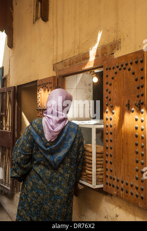 Moroccan woman buying bread in Morocco - Stock Photo