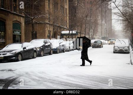 New York, NY, USA. 21st Jan, 2014. A pedestrian walks across a street during a snowstorm in New York City, the United - Stock Photo