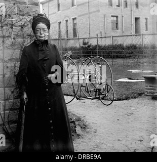 Portrait of a woman in period dress in front of an early two-seat tricycle. Photographed around 1900. - Stock Photo