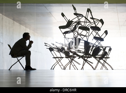 Businessman viewing office chair installation art - Stock Photo