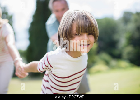 Grandparents pulling grandparents outdoors - Stock Photo