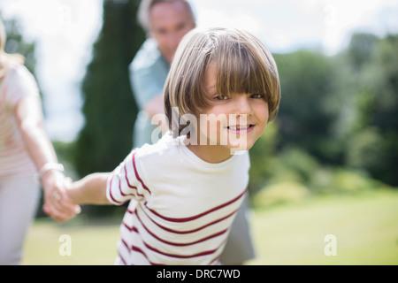 Grandparents pulling grandparents outdoors - Stock Photo