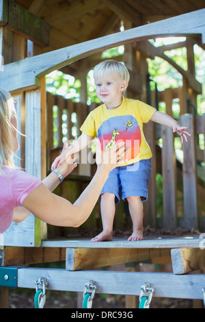 Boy jumping from playset into father's arms - Stock Photo