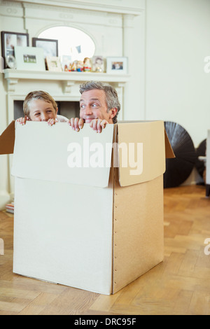 Father and son playing in cardboard box - Stockfoto