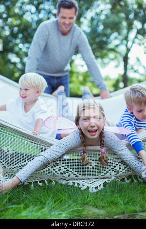 Father pushing children in hammock outdoors - Stockfoto