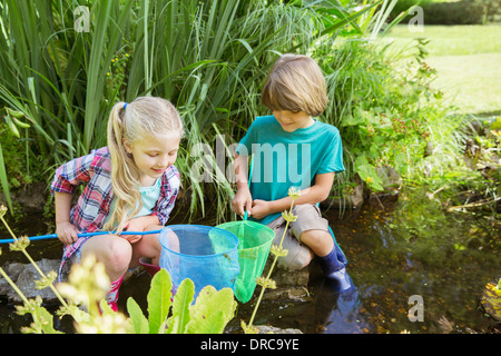 Children fishing together in pond - Stock Photo