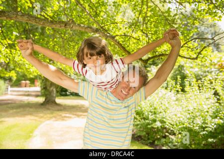 Father piggybacking son under tree - Stock Photo