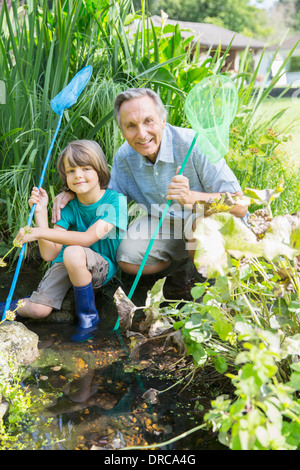 Grandfather and grandson fishing in pond - Stock Photo