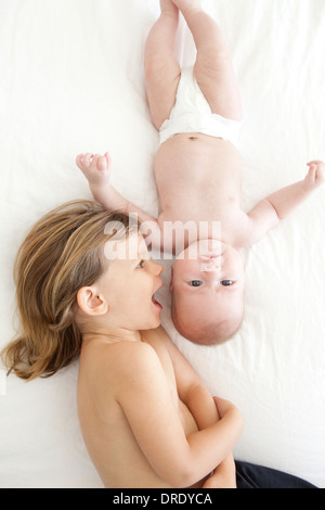 Sister kissing her younger sibling - Stock Photo