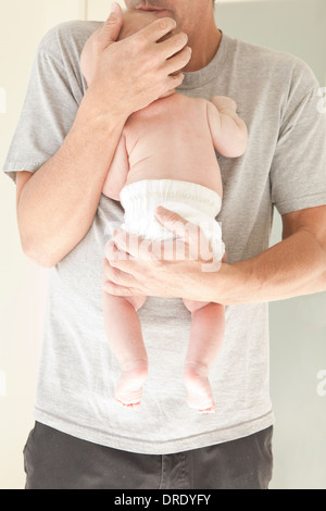 New dad holding baby in a diaper - Stock Photo