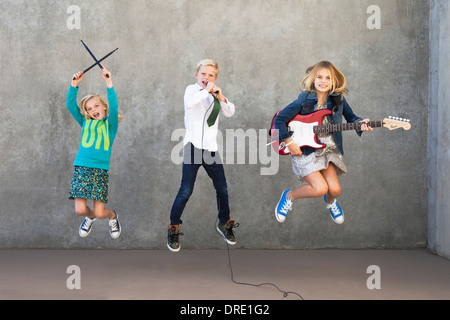 Sisters and brother rocking out - Stock Photo