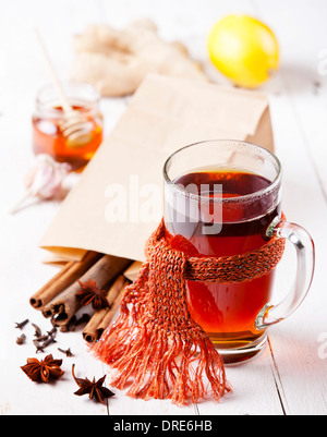Cup of Hot tea with cinnamon sticks, lemon and star anise - Stock Photo