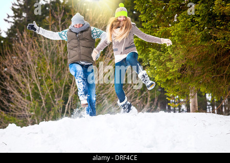Couple Jumping In Snow, Spitzingsee, Bavaria, Germany - Stockfoto